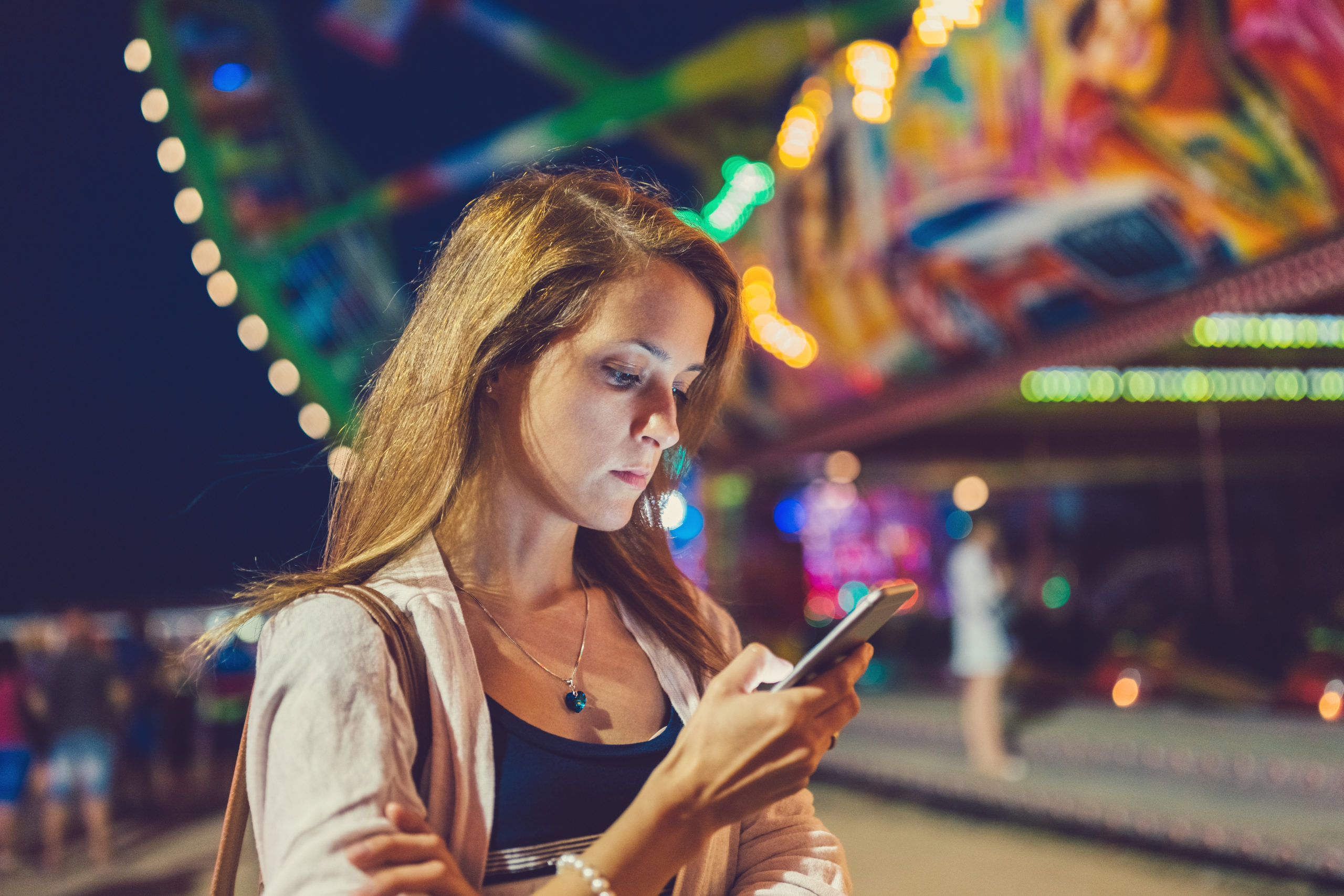 Confused girl at the amusement park using smartphone